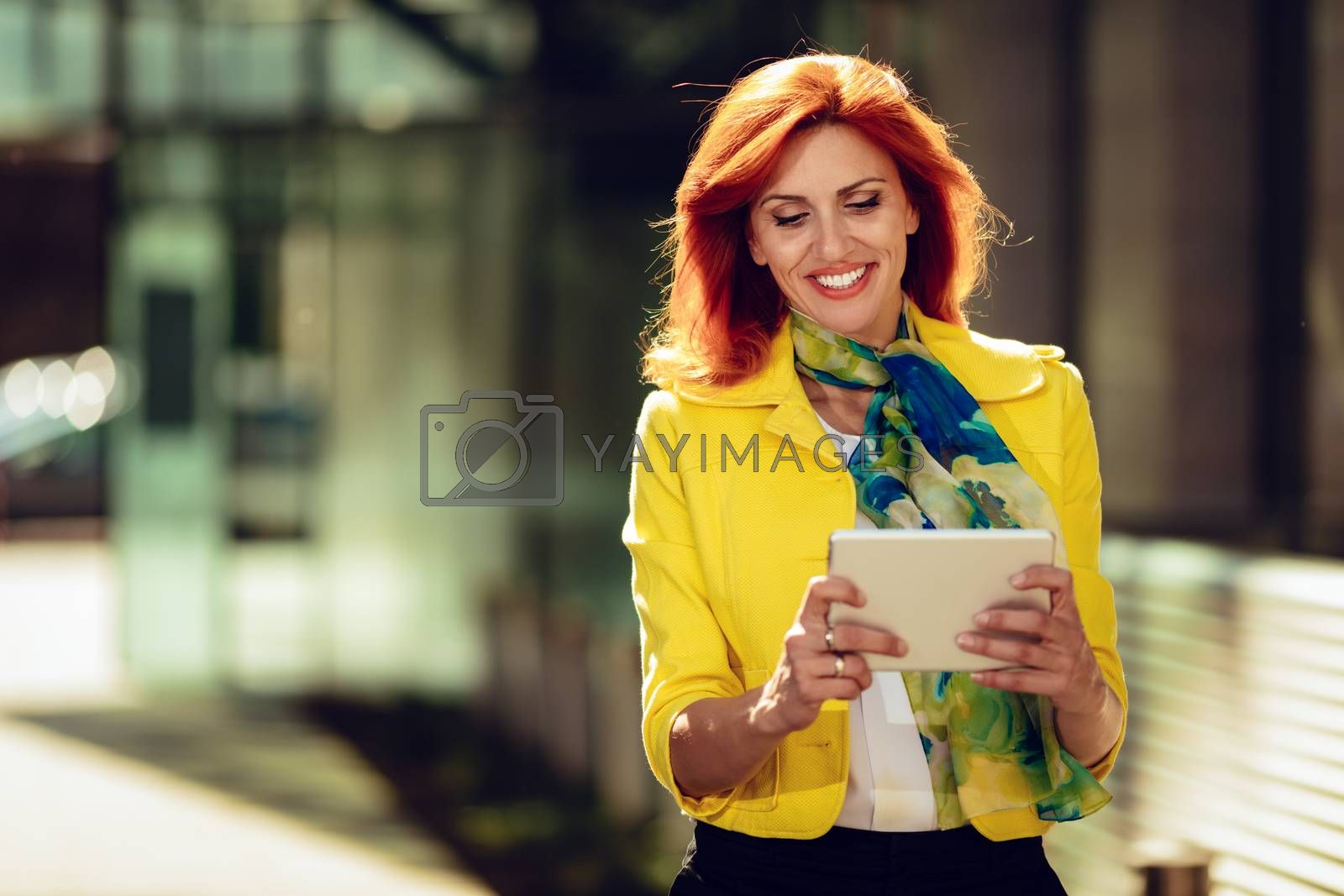 Smiling successful businesswoman using digital tablet in office district.