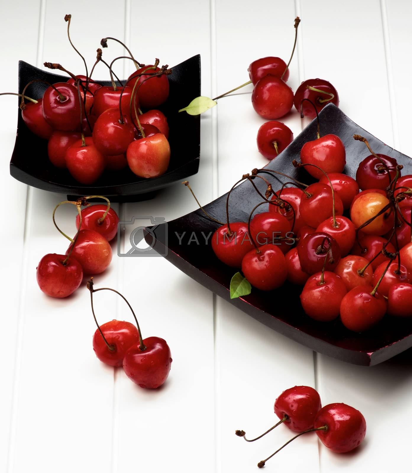 Arrangement of Fresh Ripe Sweet Maraschino Cherries in Two Black Wooden Plates closeup on Plank White background