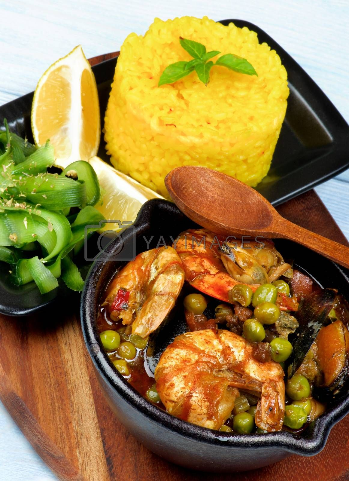 Delicious Seafood Curry with Saffron Rice, Cucumber Salad  and Lemon Served on Board closeup on Wooden background. Focus on Foreground