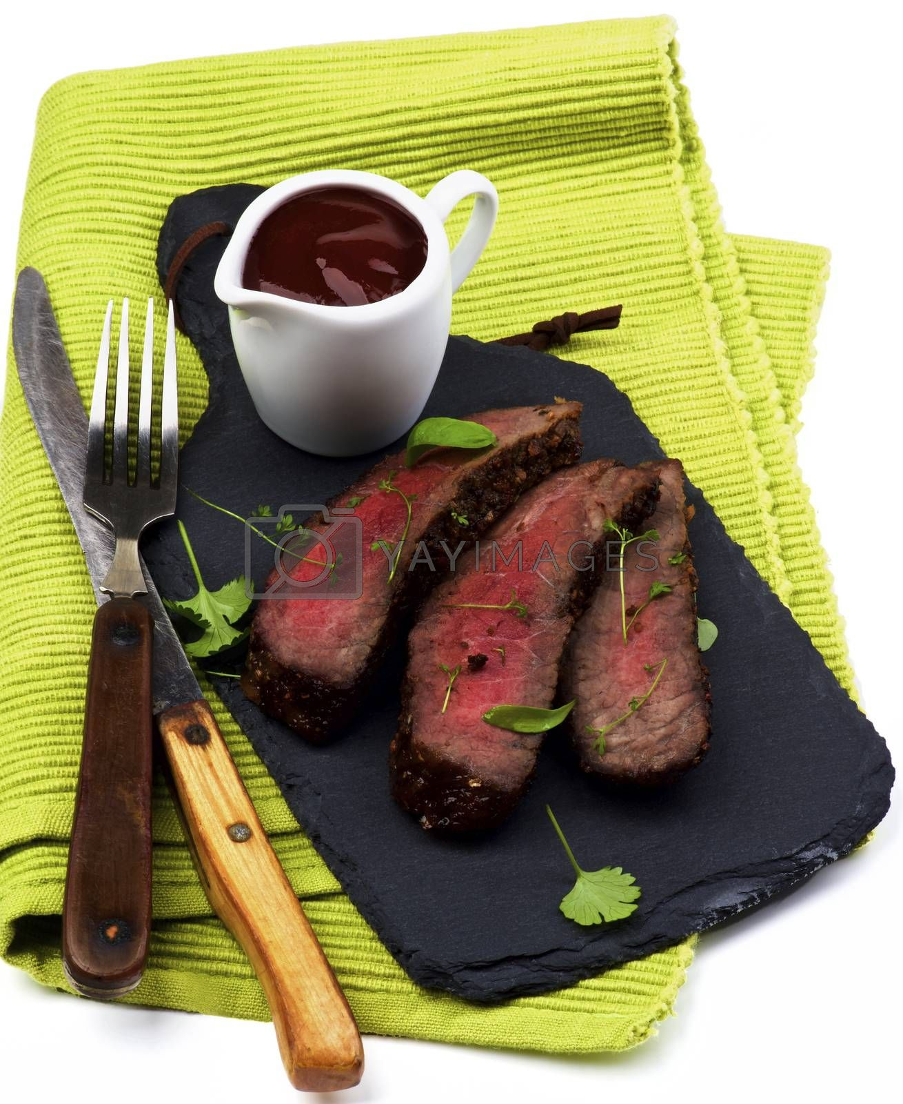 Slices of Delicious Roast Beef Medium Rare on Slate Serving Board with Tomato Sauce, Fork and Table Knife closeup on Green Napkin