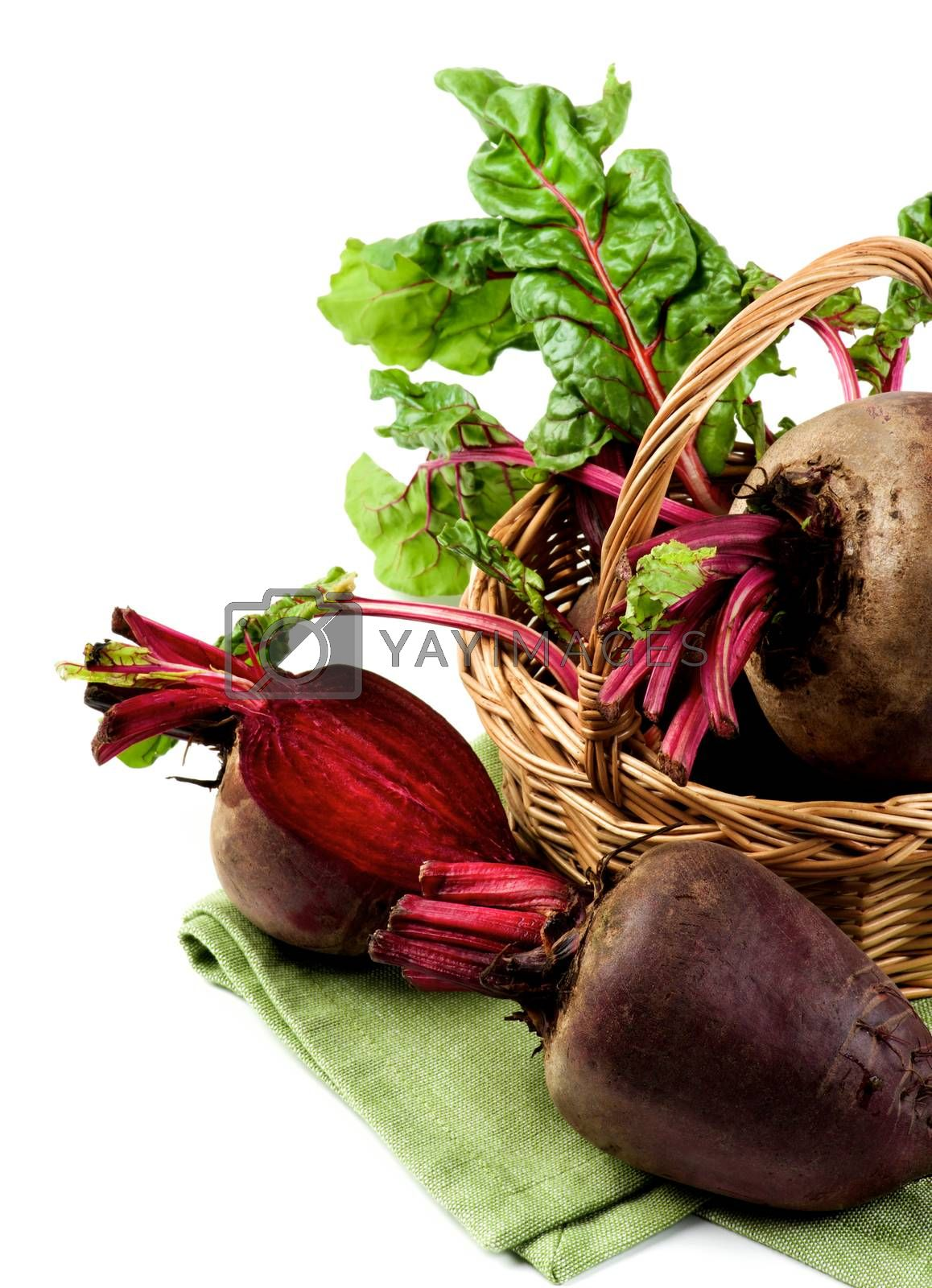 Arrangement Fresh Raw Organic Beet Roots with Green Beet Tops in Wicker Basket on Napkin isolated on White background