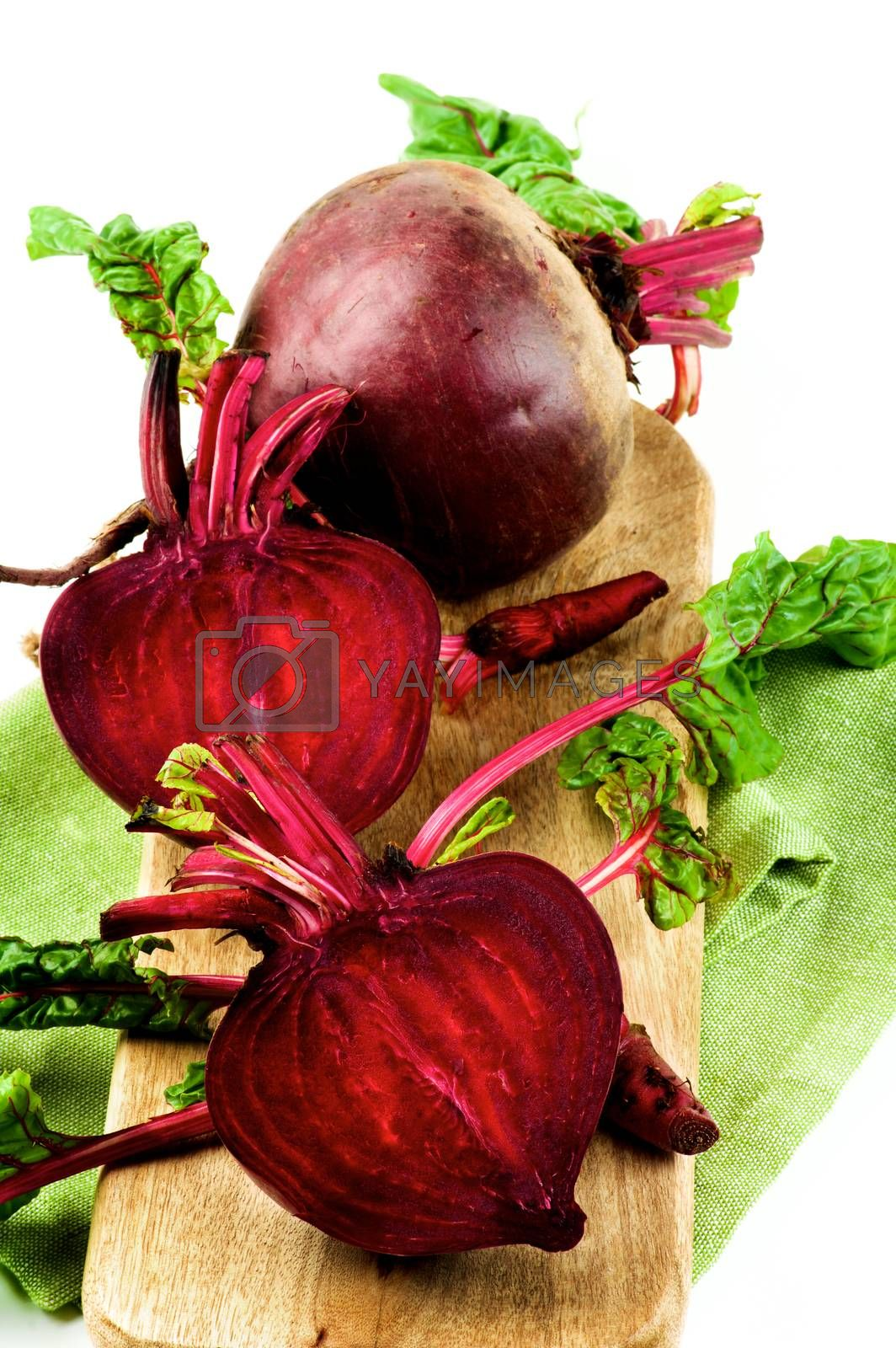 Two Halves and One Full Body Fresh Raw Organic Beet Roots with Green Beet Tops on Wooden Board and Napkin isolated on White background
