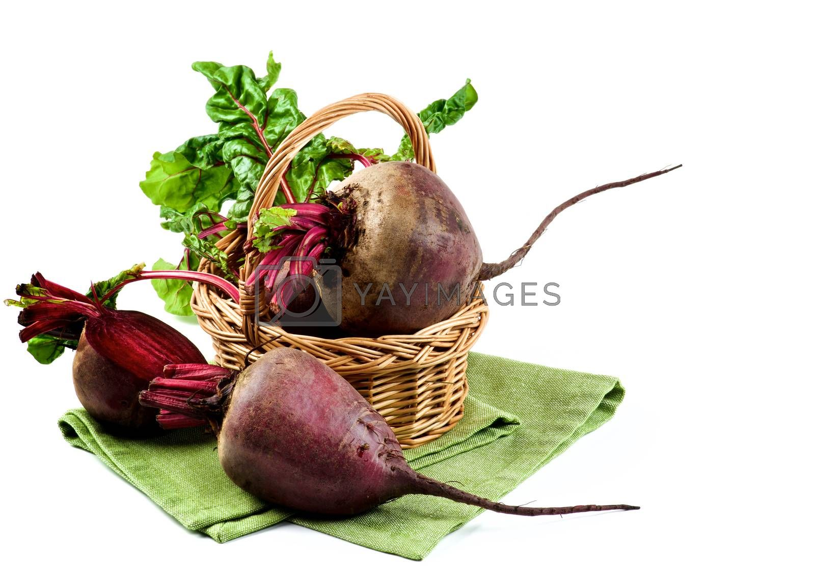 Arrangement of Full Body and Half of Fresh Raw Organic Beet Roots with Green Beet Tops in Wicker Basket on Napkin isolated on White background