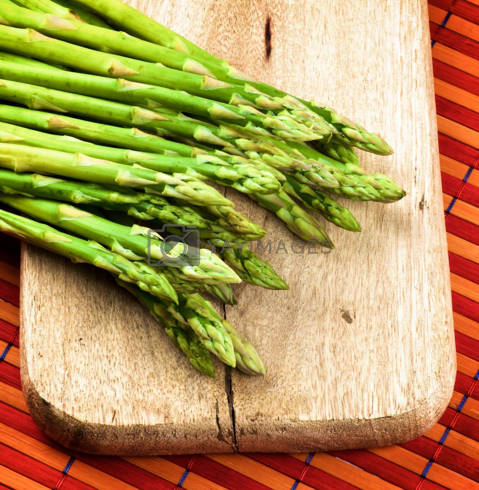 Arrangement of Fresh Raw Asparagus Sprouts on Wooden Cutting Board closeup on Orange Strawmat background