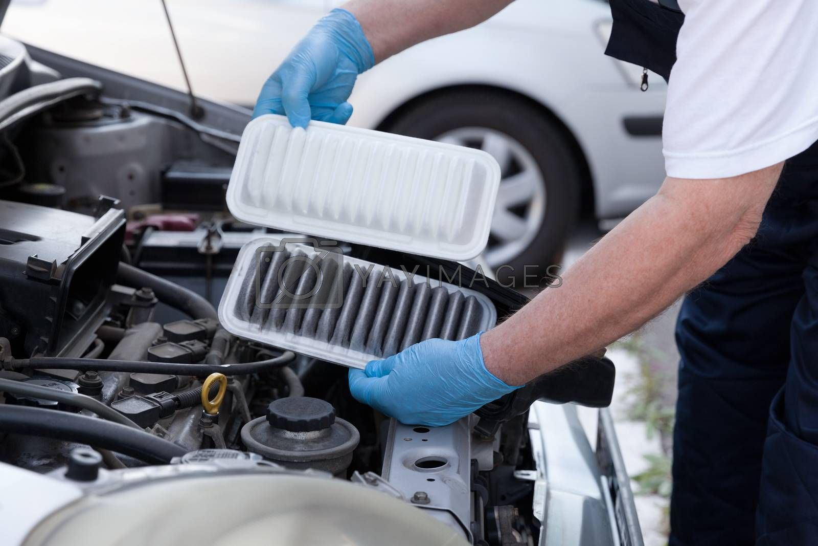 Auto mechanic wearing protective work gloves holds dirty and clean air filters over a car engine. Internal combustion engine air filters.
