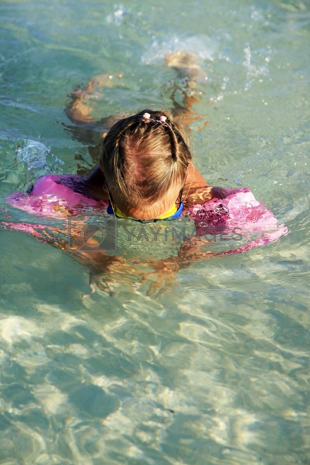Little girl dives in the clear sea by friday