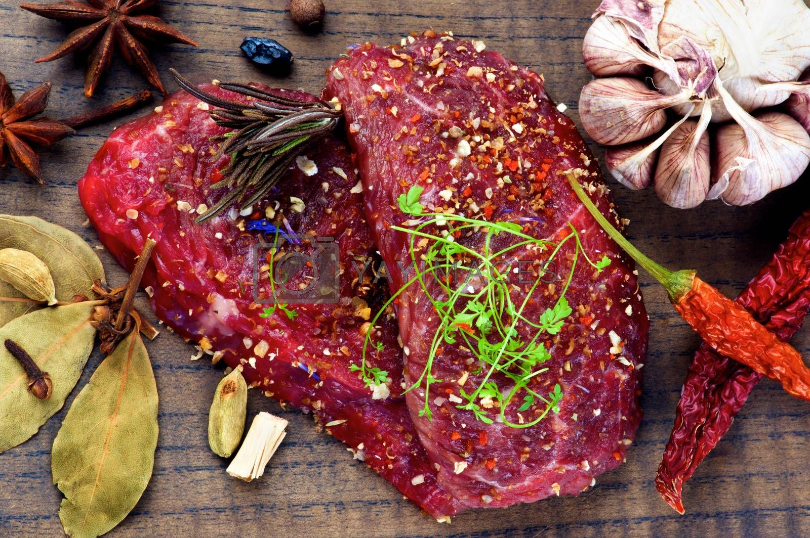 Two Marinated Raw Boneless Beef Steaks with Herbs and Spices, Garlic and Chili Pepper closeup on Wooden Cutting Board. Top View