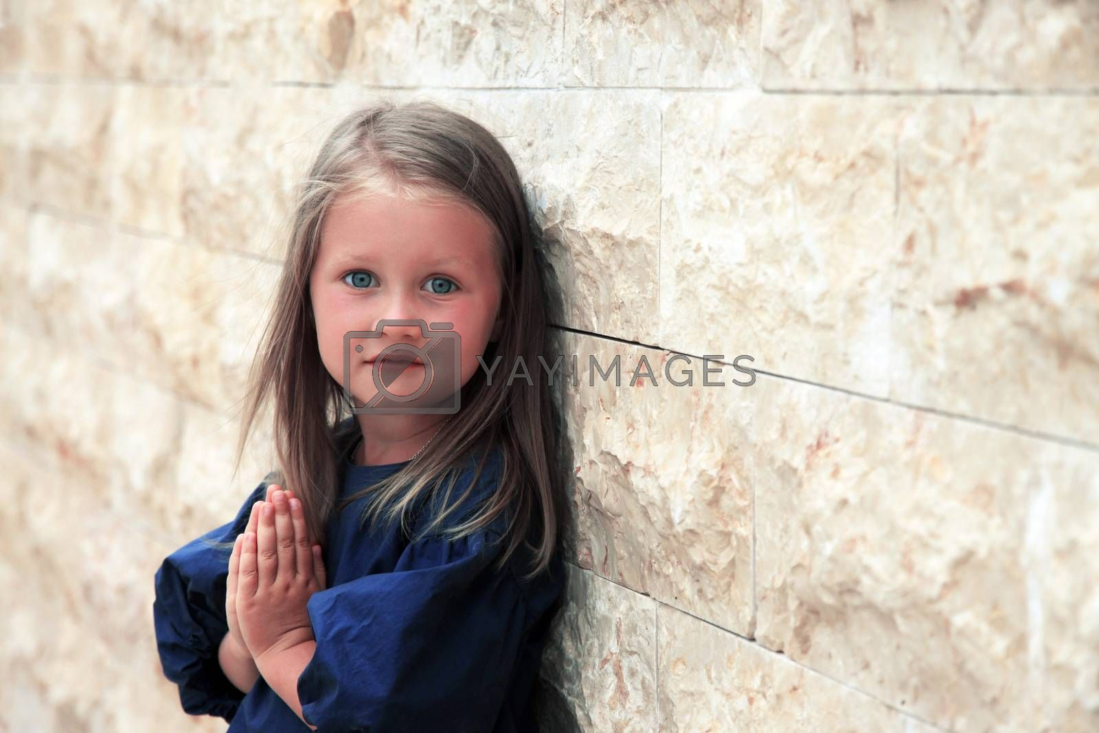 Little girl laughing in the background of stone wall