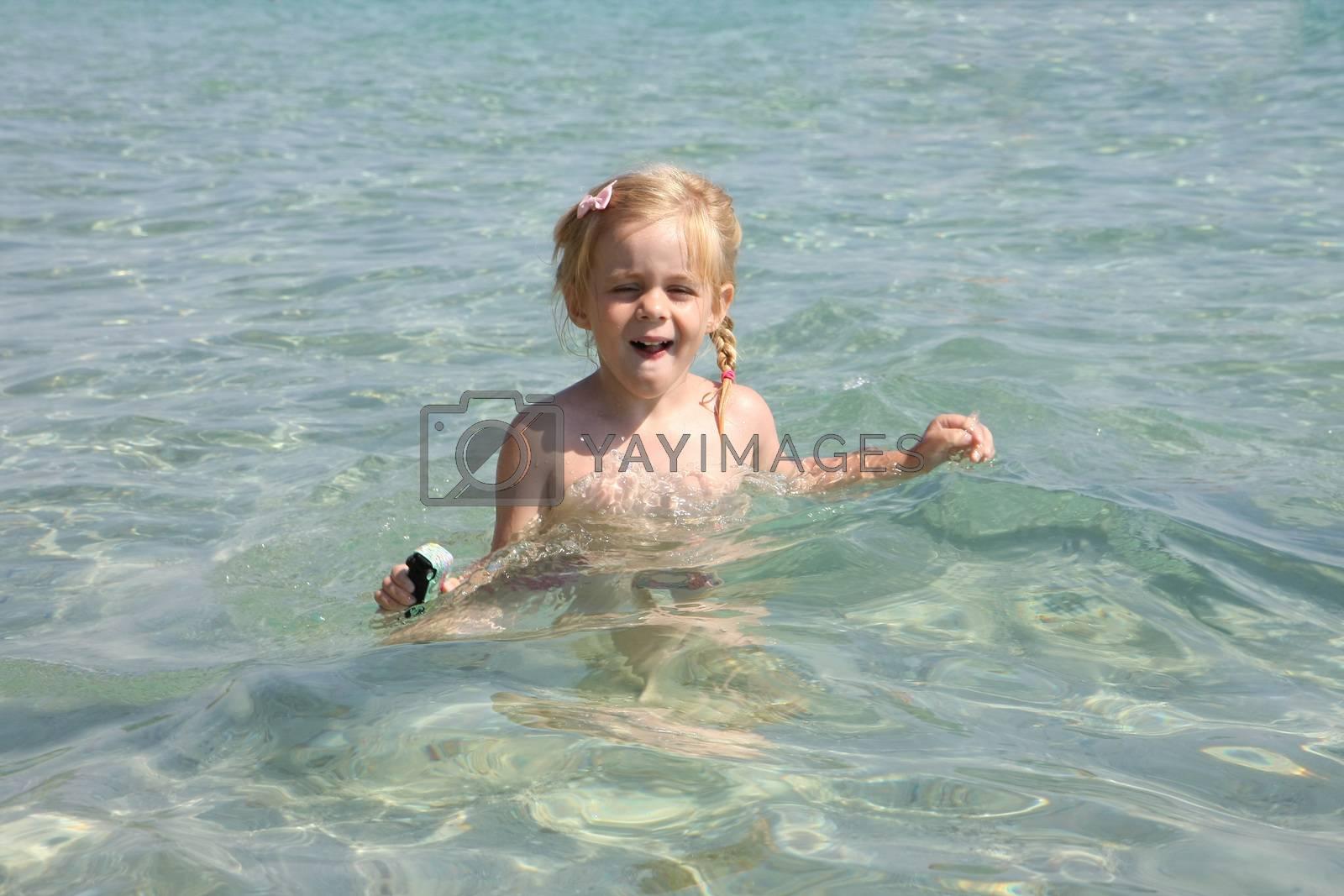 Baby girl enjoying in the clear sea water