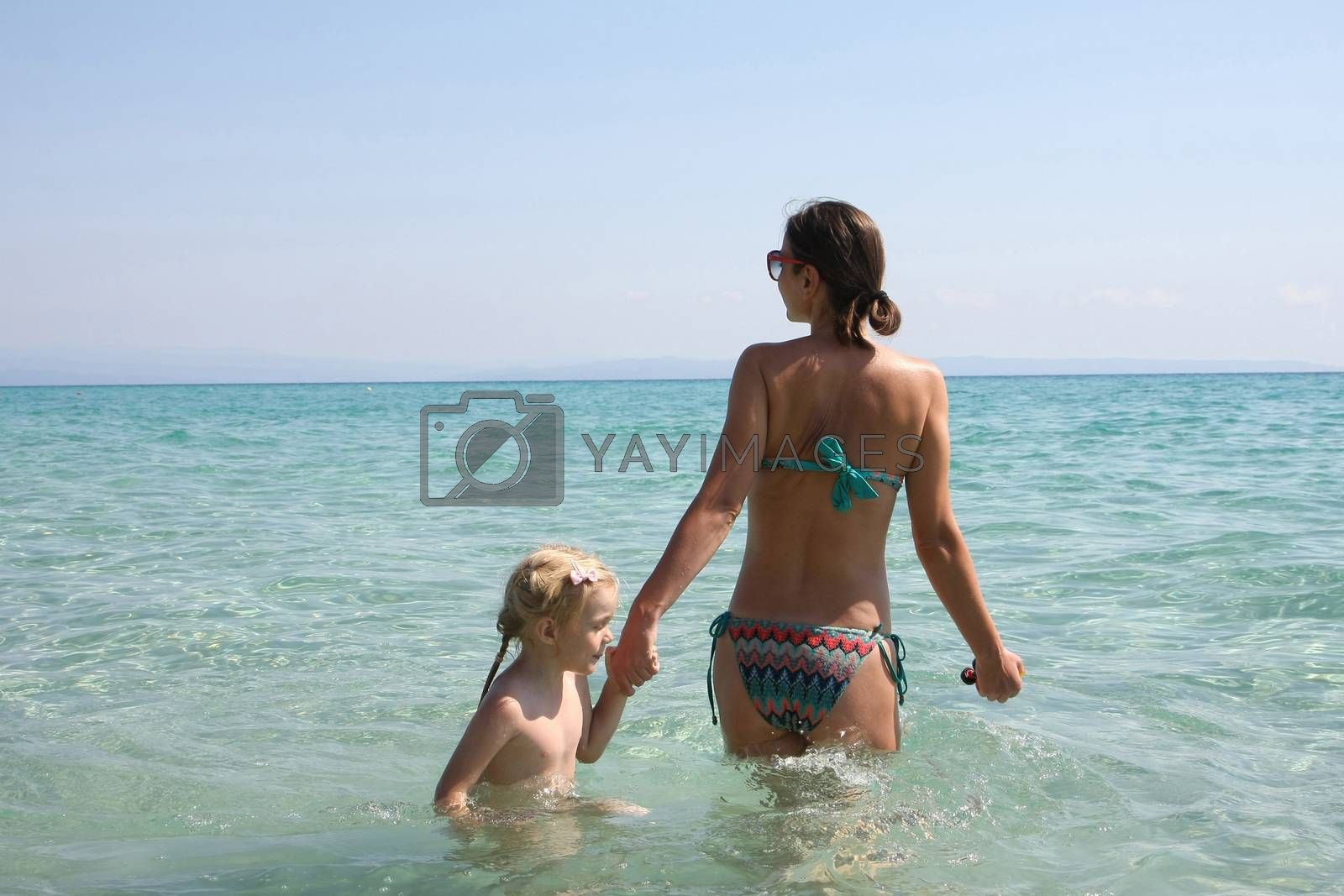 Mother and daughter enjoying in the clear sea water