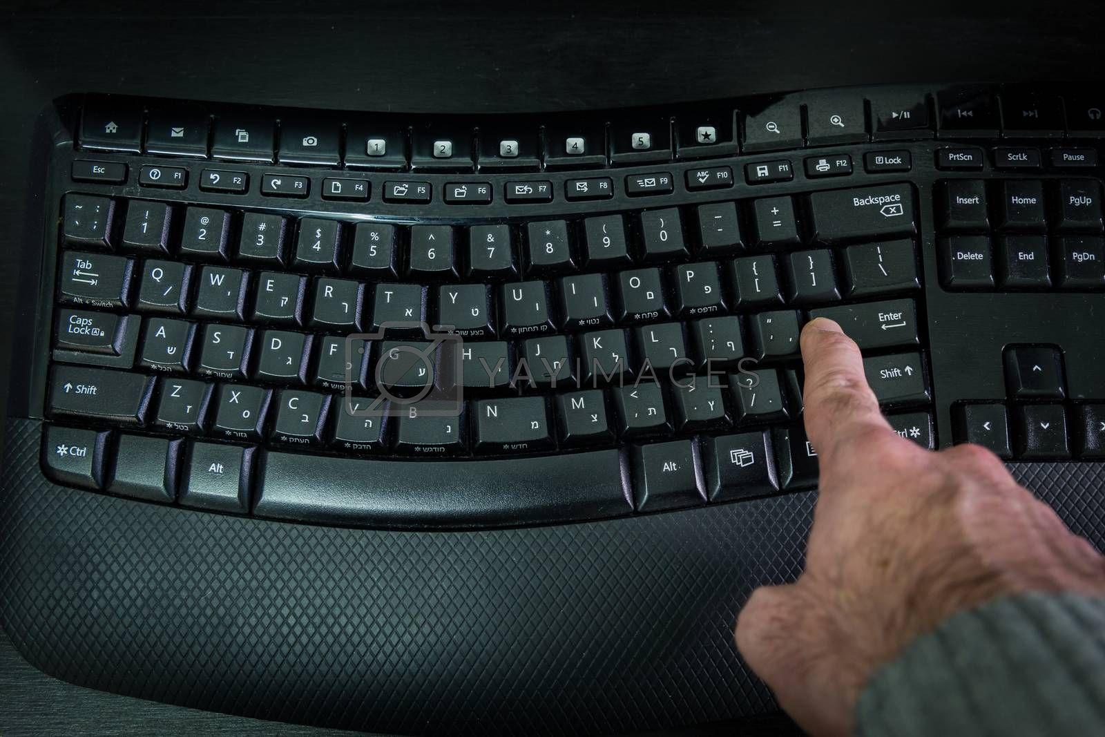 Man typing on a Wireless keyboard with letters in Hebrew and English - Press the Enter key - Top View - Dark atmosphere