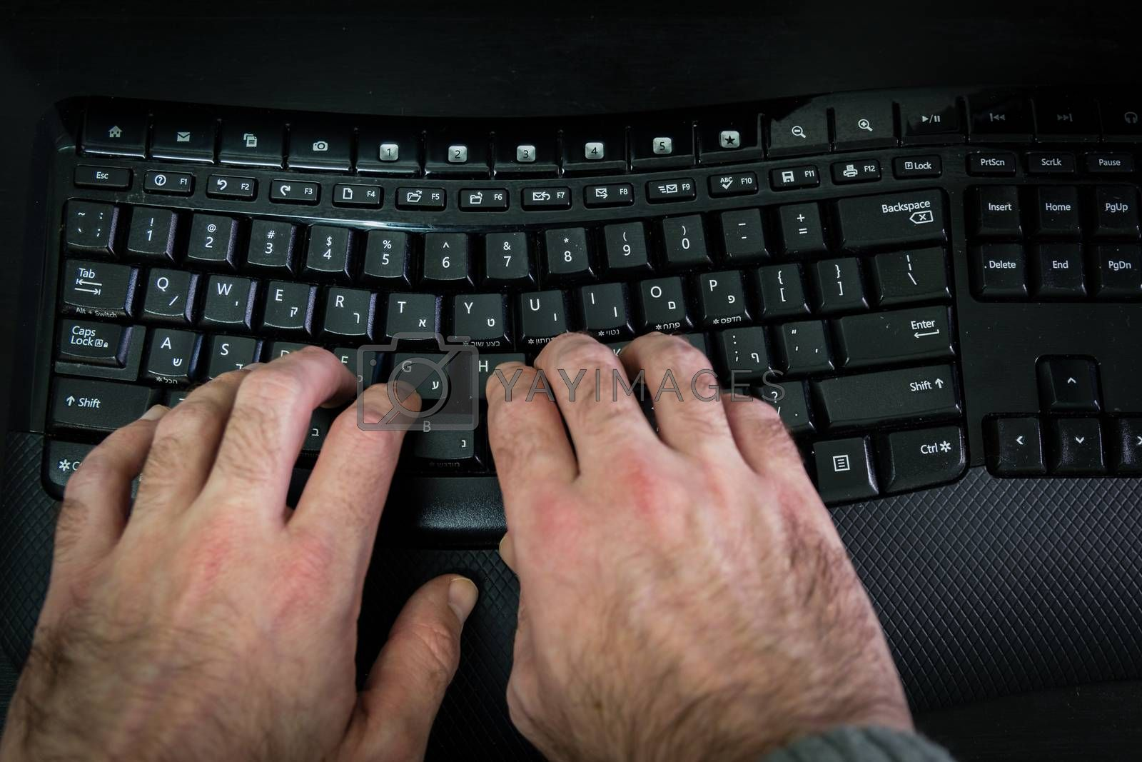 Man typing on a keyboard with letters in Hebrew and English - Wireless keyboard - Top View - Dark atmosphere