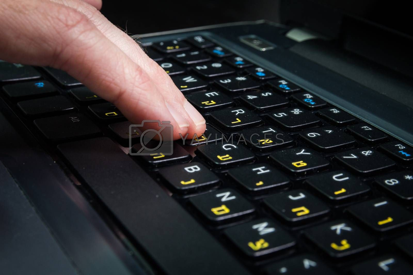 Man typing on a keyboard with letters in Hebrew and English - Laptop keyboard - Close up_Dark atmosphere