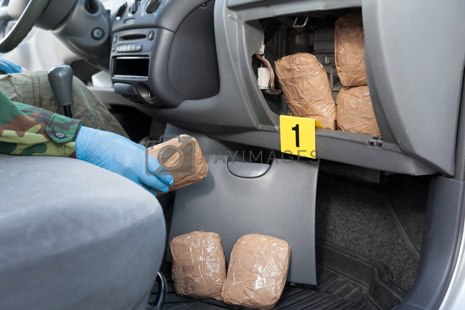 Policeman holding drug package discovered in secret compartment in a car
