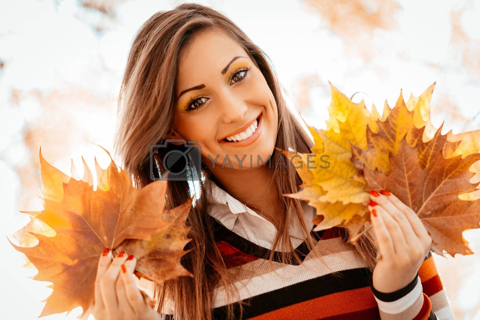 Portrait of a cute young woman enjoying in sunny forest in autumn colors. She is holding golden yellow leaves. Looking at camera.