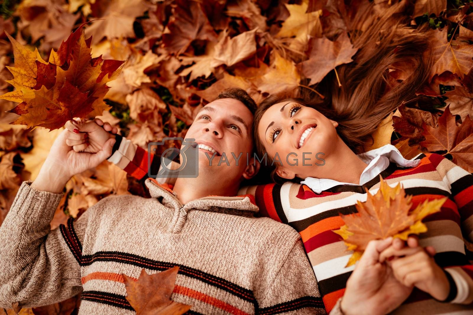 Beautiful young couple in sunny forest in autumn colors. They are lying on the ground covered with leaves and enjoying.