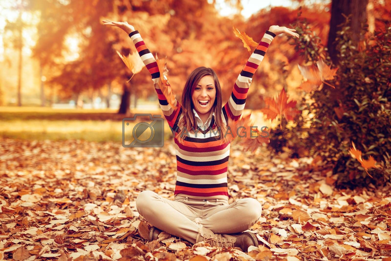 Cute young woman enjoying in sunny forest in autumn colors. She is sitting on the ground covered with leaves and having fun.