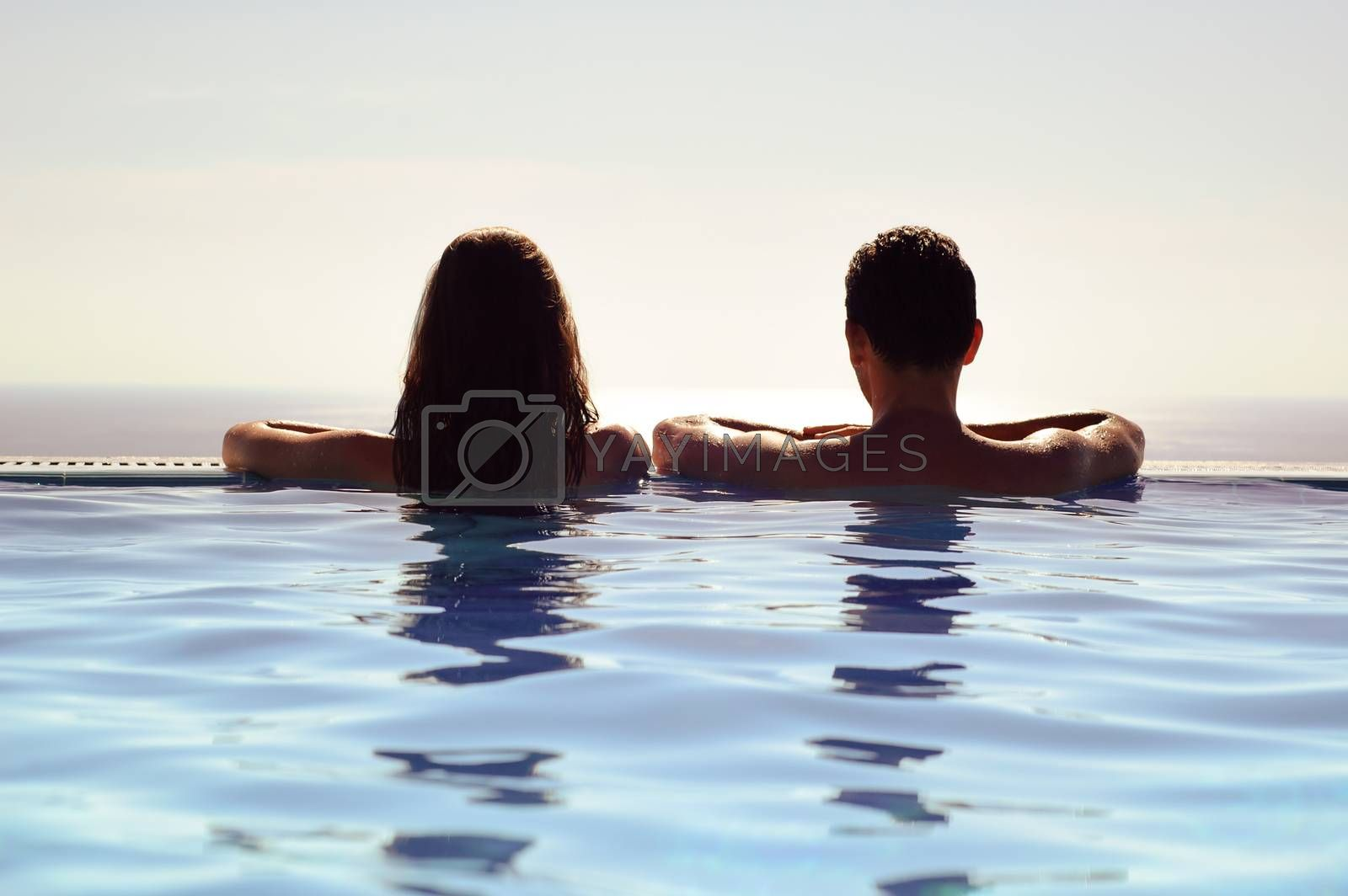 Young Couple Relaxing Together in an Infinity Swimming Pool and Enjoying the View of Horizon and Sea. Rear View of Honeymoon Couple at Luxury Resort. Travel and Summer Vacation.