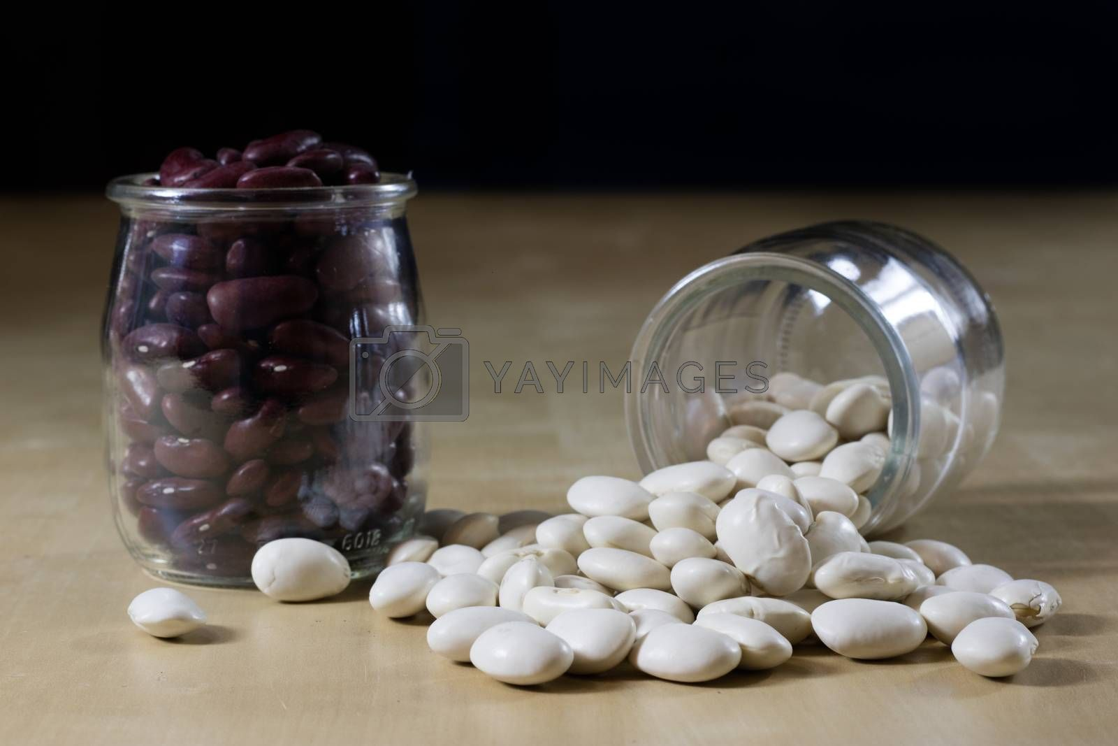 Delicious bean in a glass jar on a wooden kitchen table. Black background.