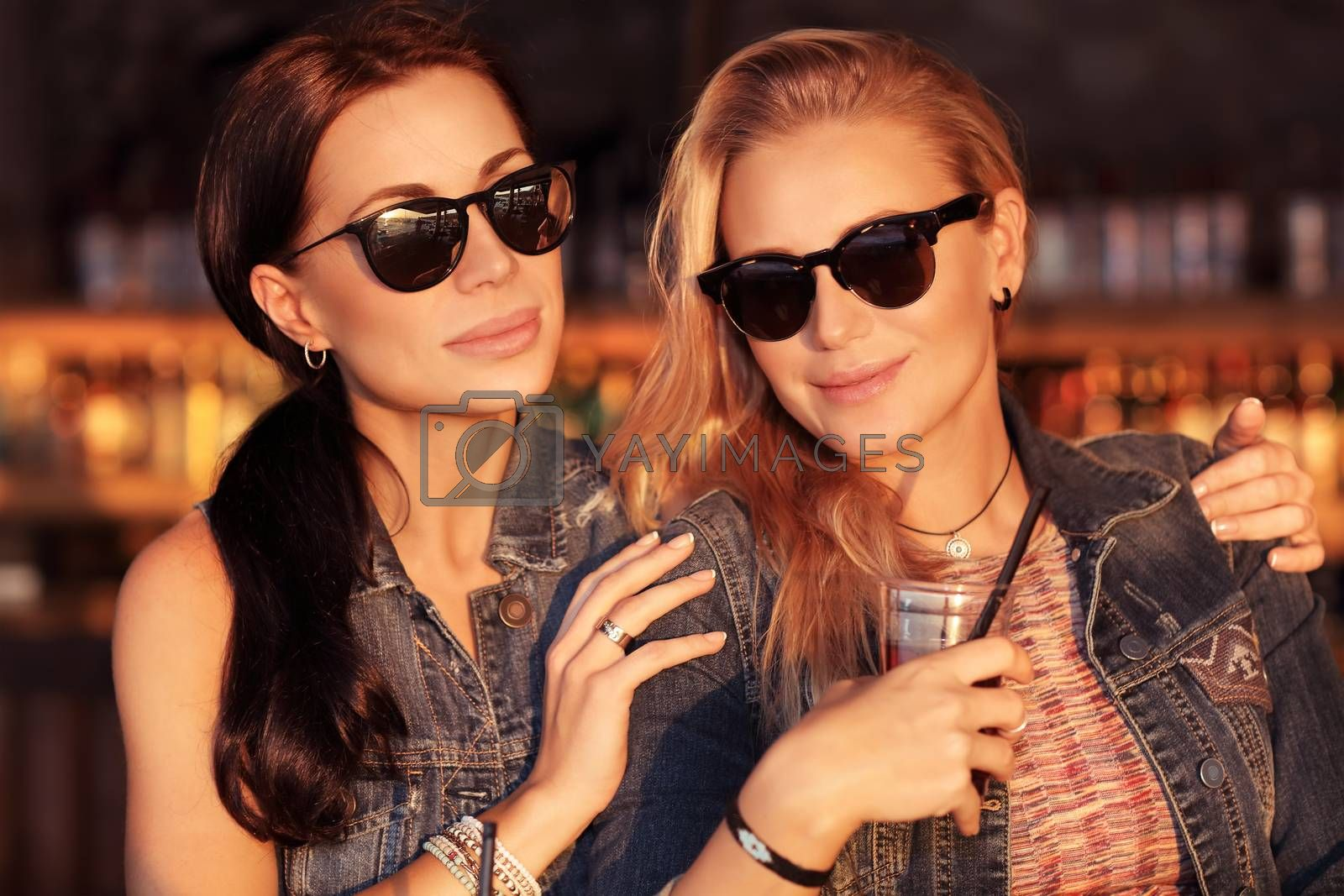 Portrait of a two beautiful girlfriends spending time outdoors, street fashion look of a two gorgeous women, friendship