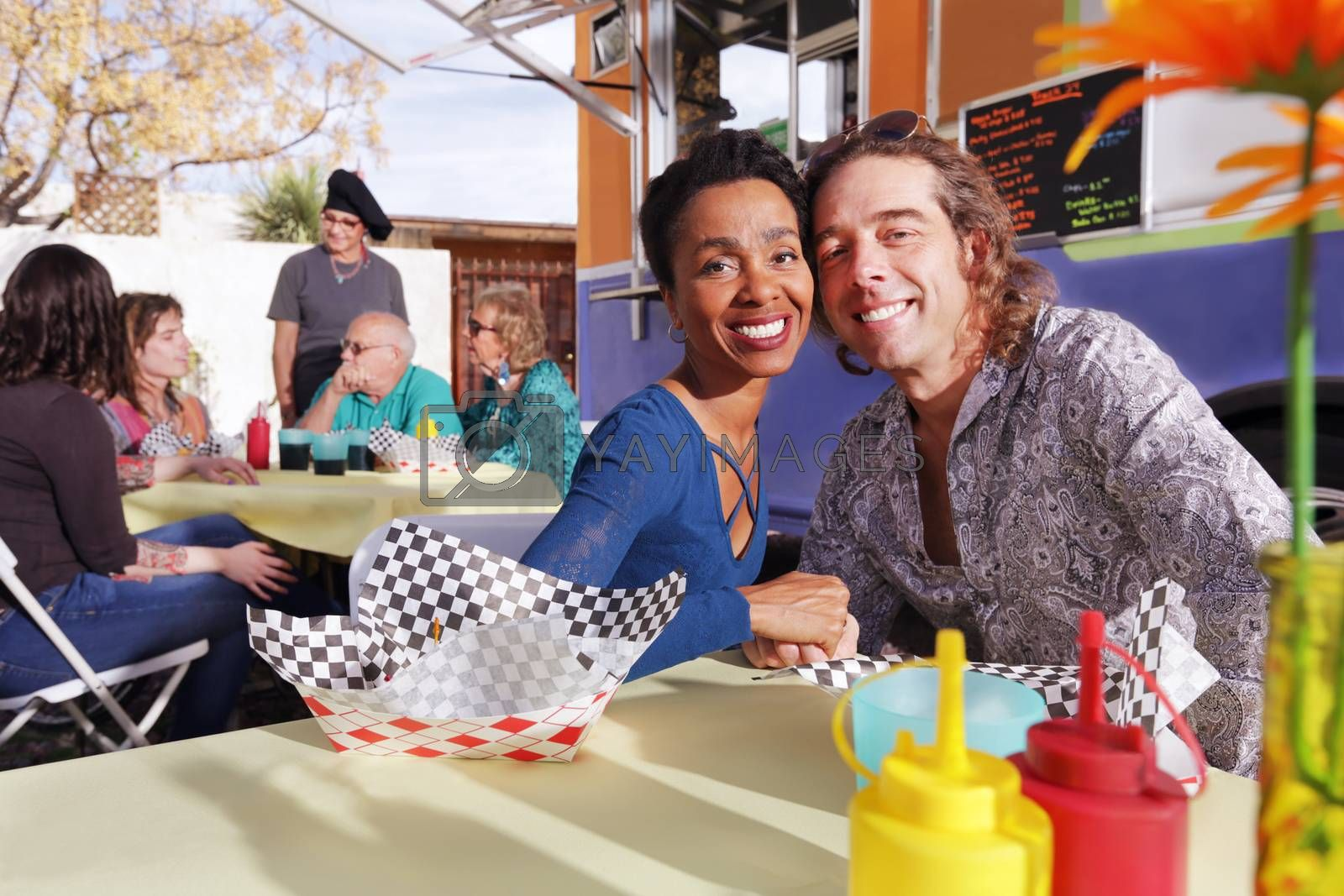 Handsome diverse couple smiles at camera while seated at an outdoor table beside a food truck
