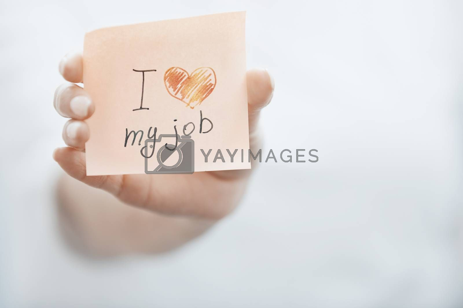 Hand of woman holding adhesive note with text