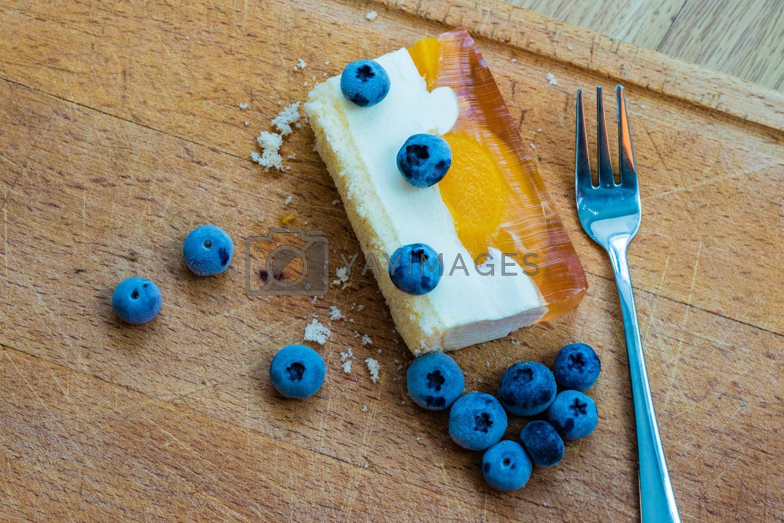 Delicious and sweet cake with blueberries. Sunny dessert on the kitchen table. Light background.