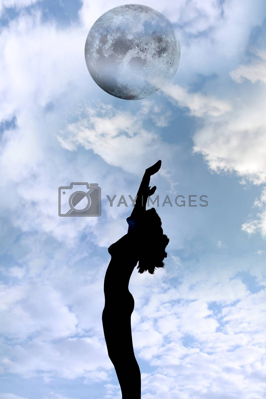 attractive silhouetted nude woman holding her hands up to the sky giving gratitude to the moon in a yoga pose with a cloudy background