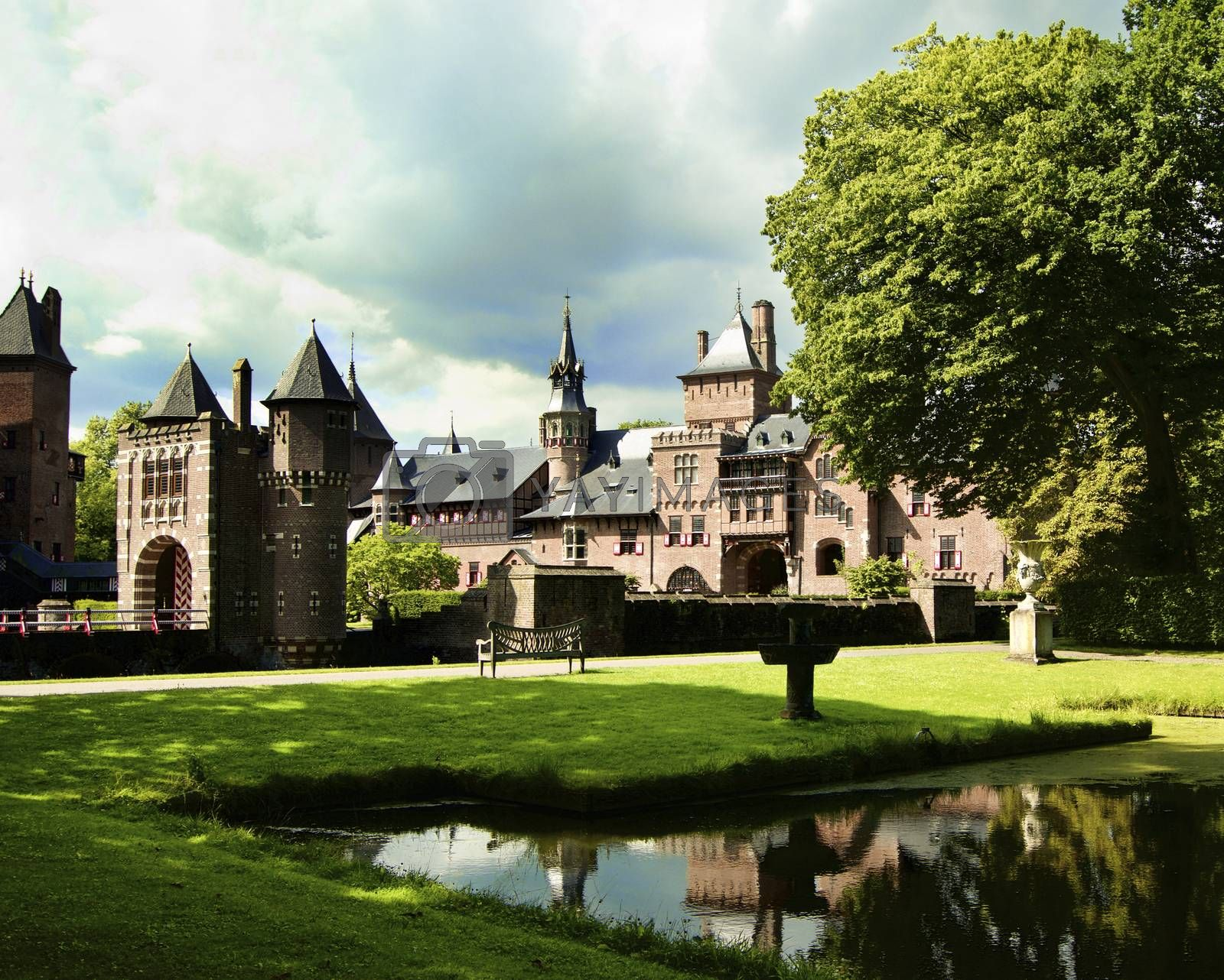 Medieval Castle De Haar from side of Back Yard with Reflection on Pond against Cloudy Sky Outdoors. Utrecht, Netherlands