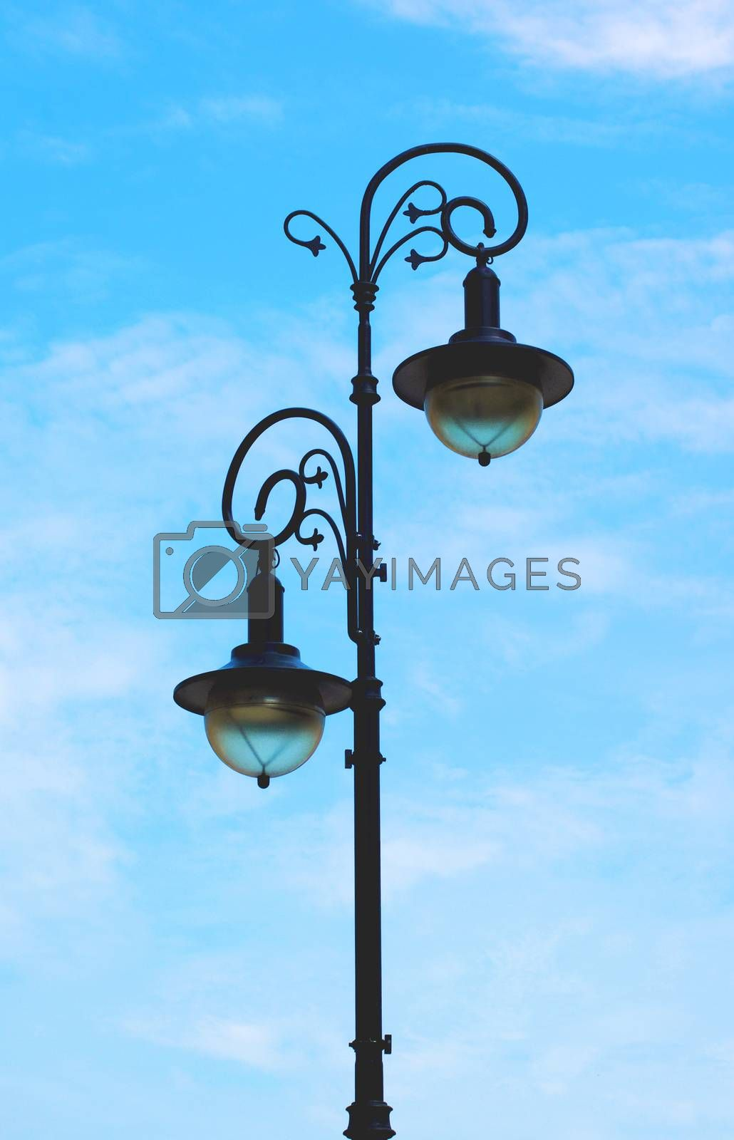 Elegant Street Lantern with with Forged Curled Details against Blue Cloudy Sky Outdoors