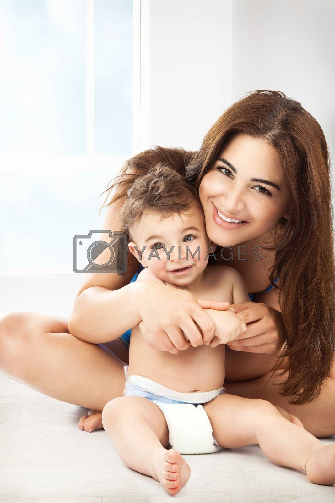 Cheerful young mother with her cute little son playing at home, with pleasure spending time together, happy family life