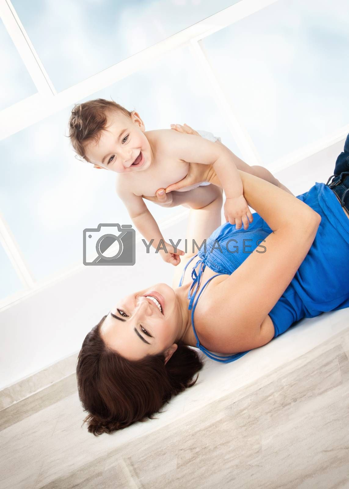 Cheerful joyful mother playing with her adorable son, lying down on the floor at home, enjoying motherhood, happy family life