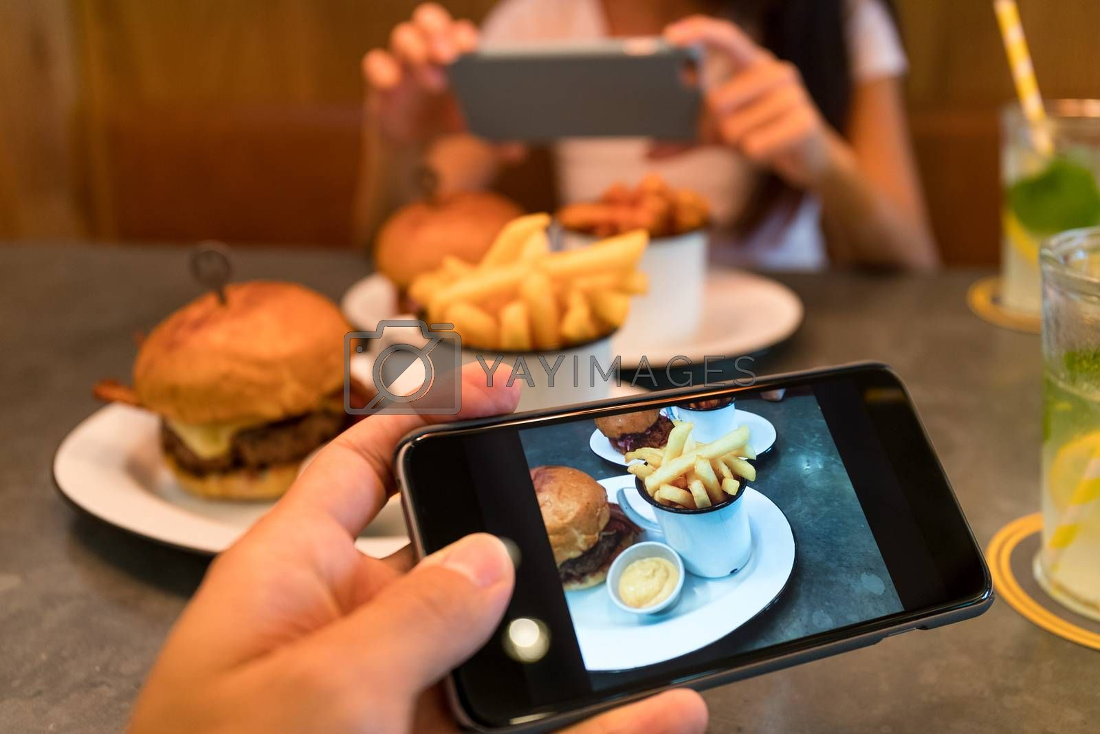 Royalty free image of Taking photo on cellphone in restaurant by leungchopan