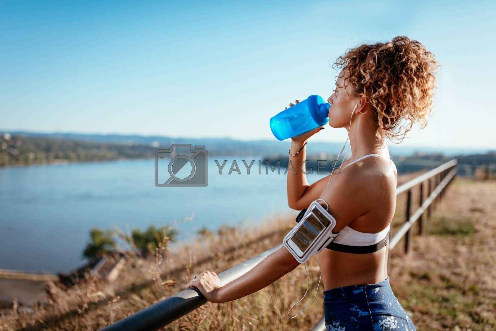 Young urban runner woman with headphones resting after jogging and drinking water on the city rooftop.