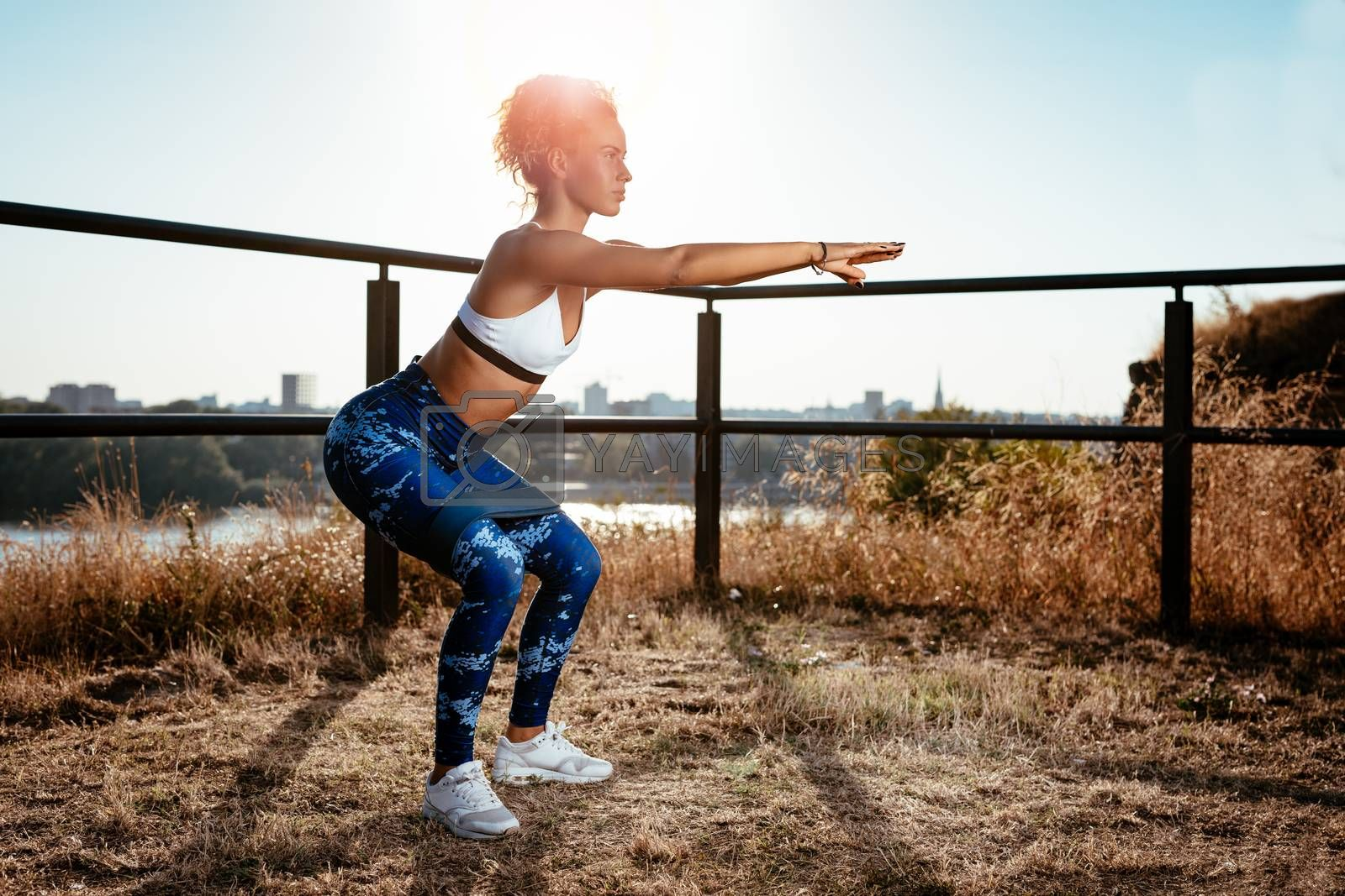 Young fitness woman doing exercise on the city rooftop.