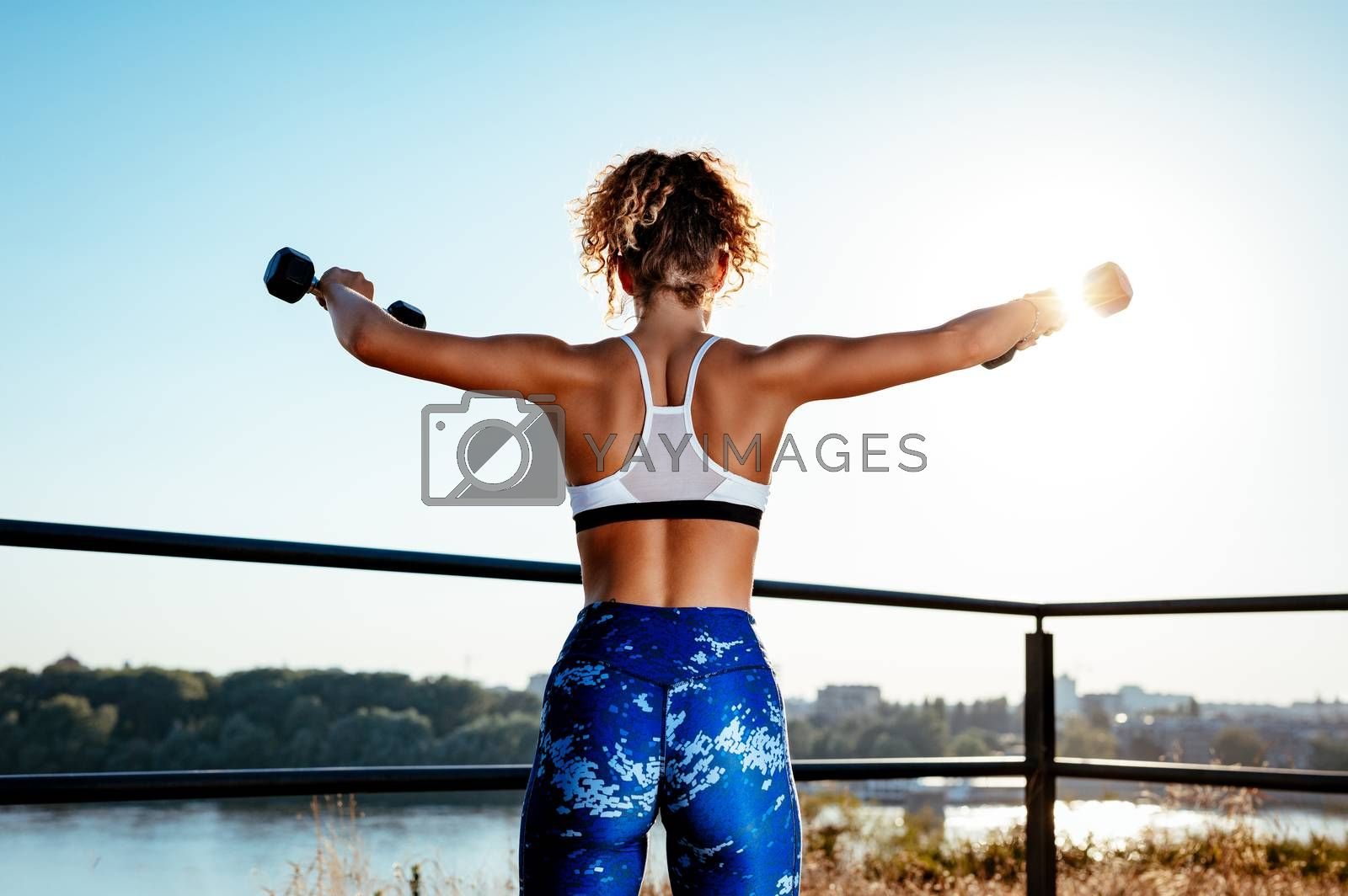 Young fitness woman doing exercise with dumbbell on the city rooftop. Rear view.