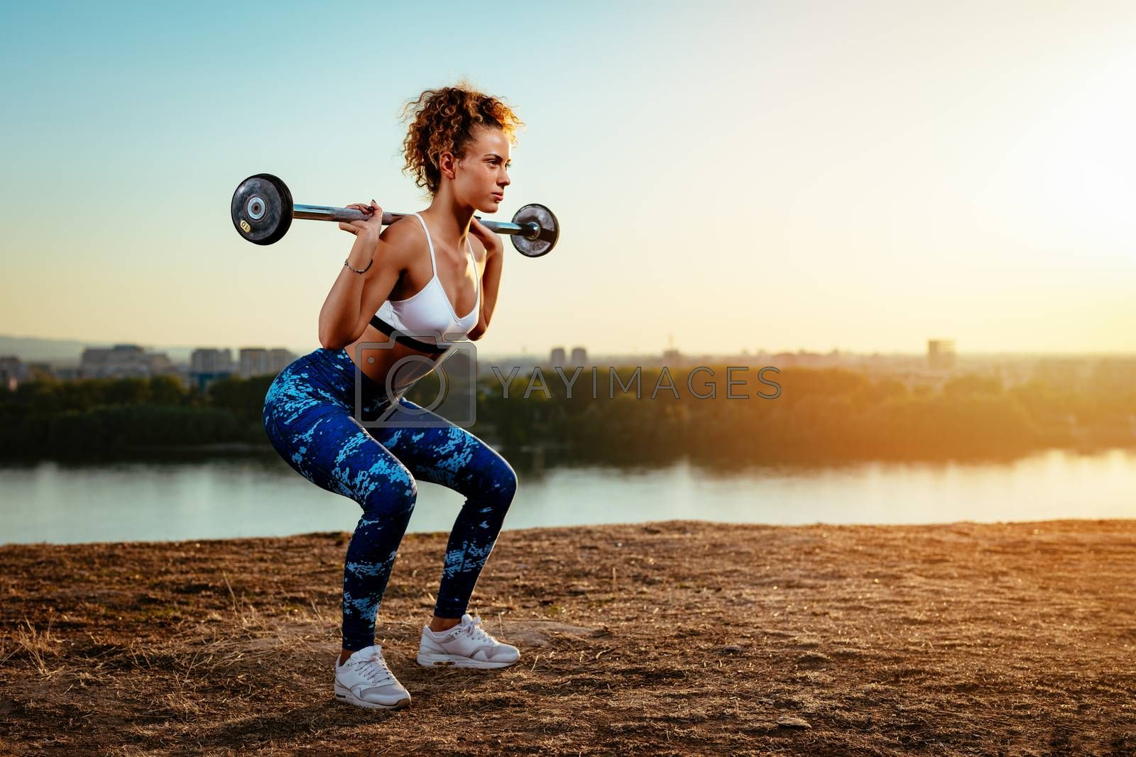 Young fitness woman doing workout with dumbbell by river on the city rooftop.