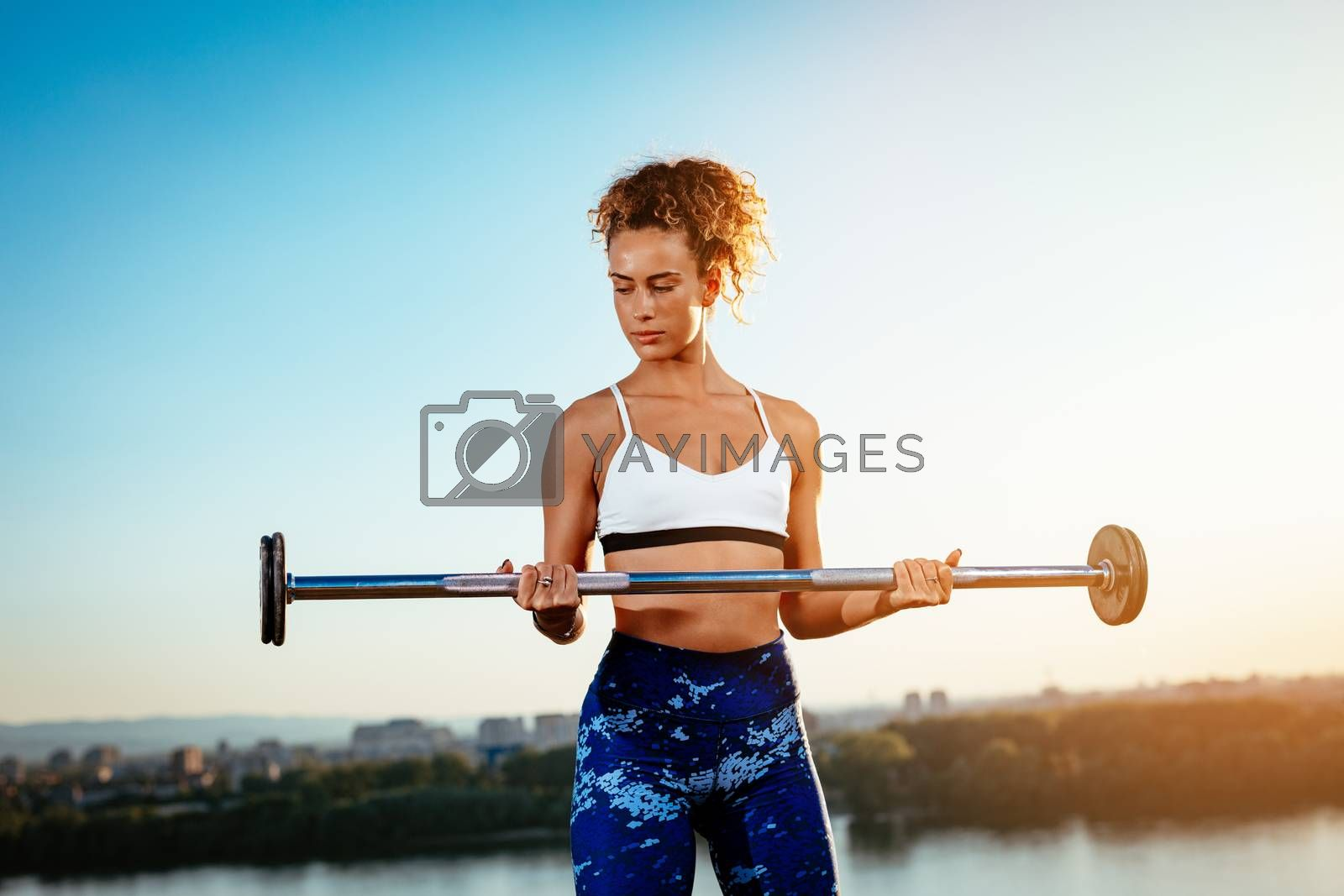 Young fitness woman doing exercise with dumbbell on the city rooftop.