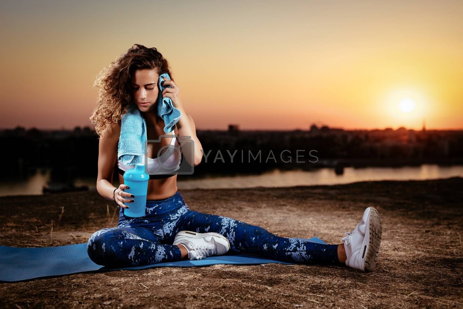 Young fitness woman resting afther hard training on the city rooftop at sunset.