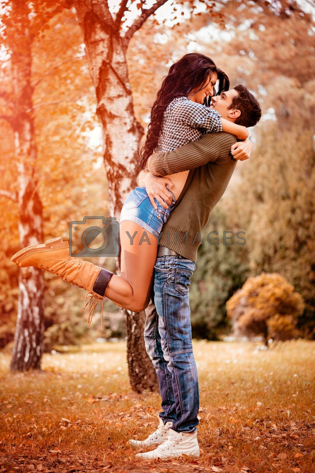 Beautiful lovely couple enjoying in sunny park in autumn colors. Guy holding girlfriend in height in a passionate embrace.