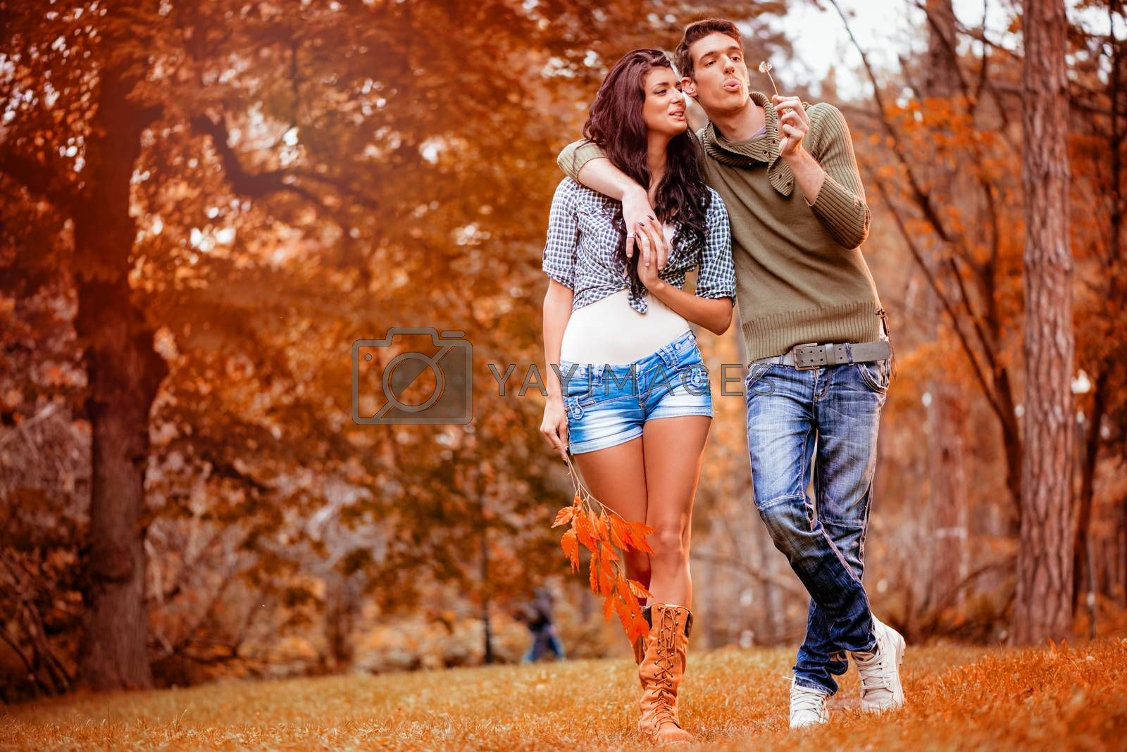 Beautiful lovely couple walking and enjoying in the park in autumn colors.