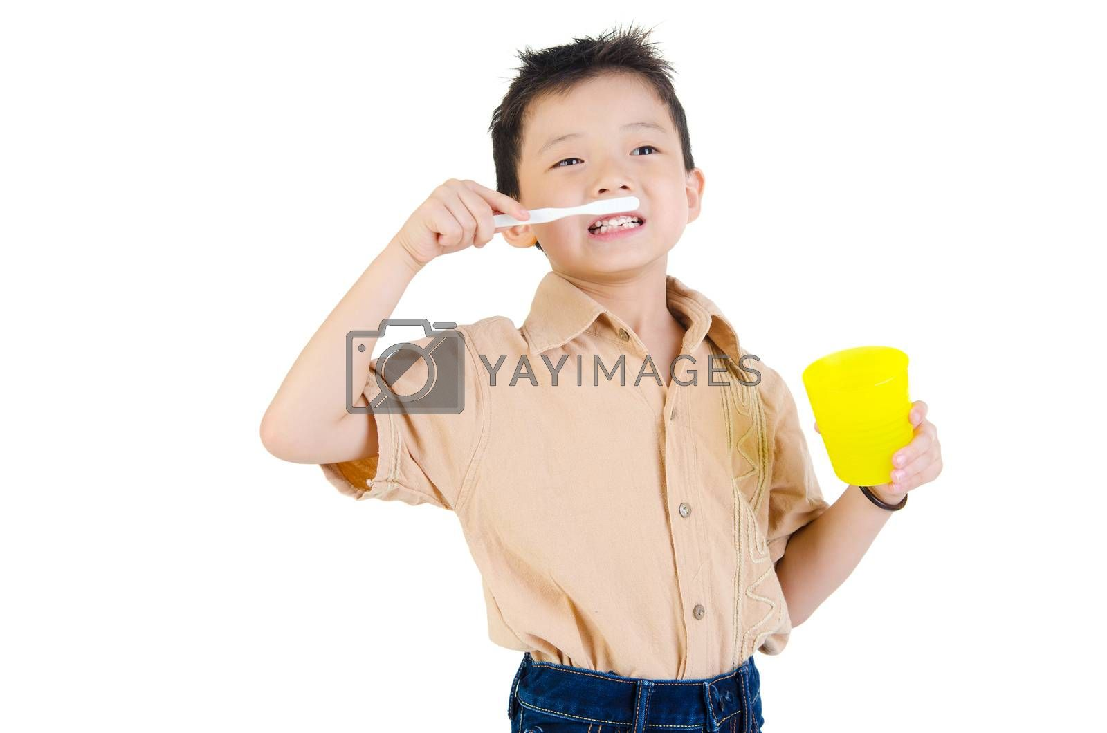 Closeup cute asian boy with a toothbrush in hand smiling and go to brush teeth oral health concept. Isolated on white background.