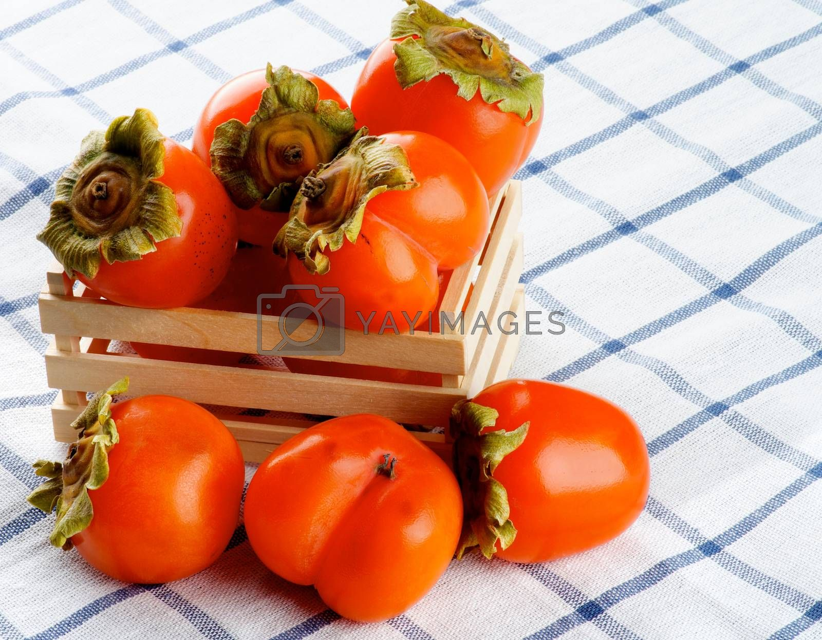 Arrangement of Delicious Raw Persimmon in Wooden Box closeup on Checkered Textile Napkin