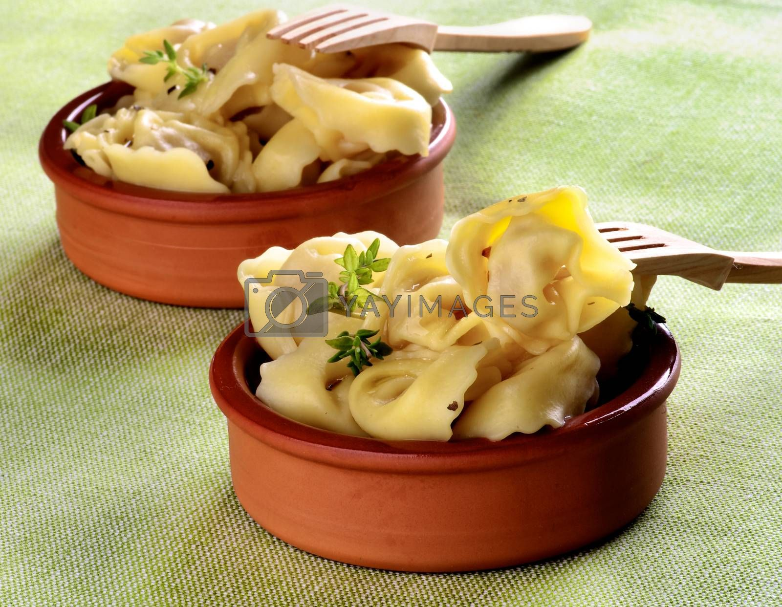 Delicious Meat Cappelletti with Herbs in Ceramic Bowls with Wooden Forks closeup on Green Napkin background