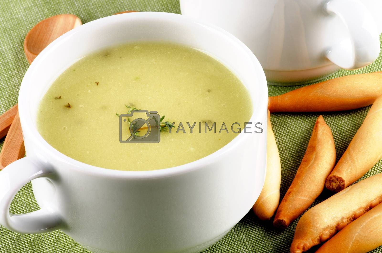 Delicious Cream Asparagus Soup in White Soup Cup with Bread Sticks and Wooden Spoon closeup on Green Napkin