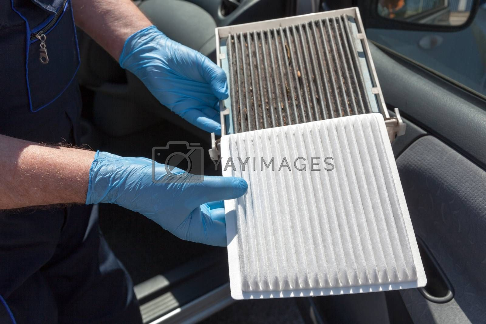Replacing the pollen air filter. Old and new cabin air filter for a car.