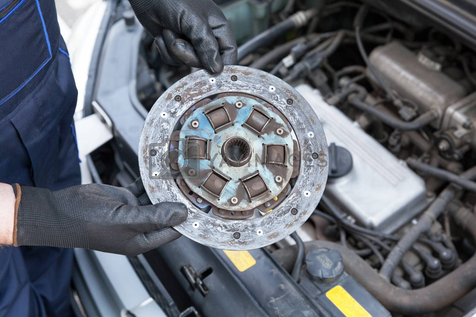 Auto mechanic wearing protective work gloves holding old clutch disc over a car engine