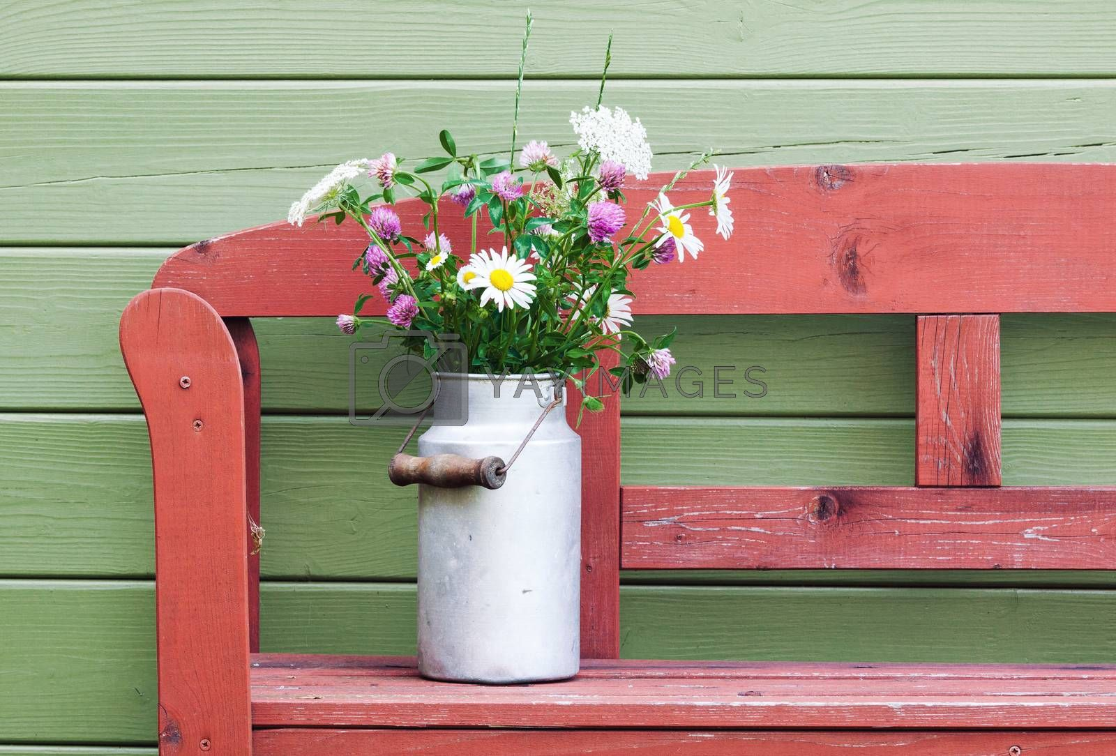 Beautiful bouquet of field flowers in vintage aluminum milk can