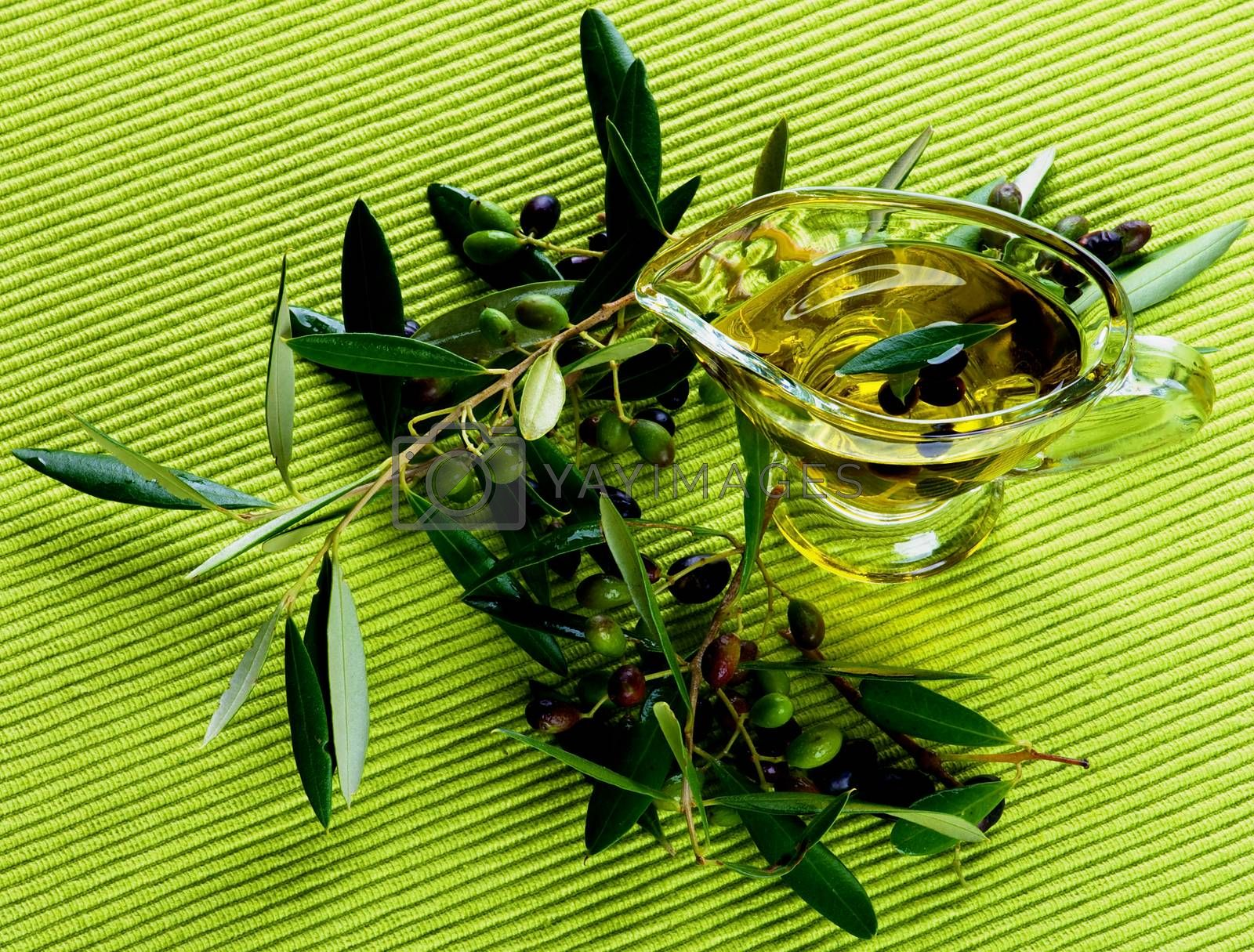 Fresh Olive Oil in Glass Gravy with Raw Green and Black Olives with Leafs on Green Textile background. Top View