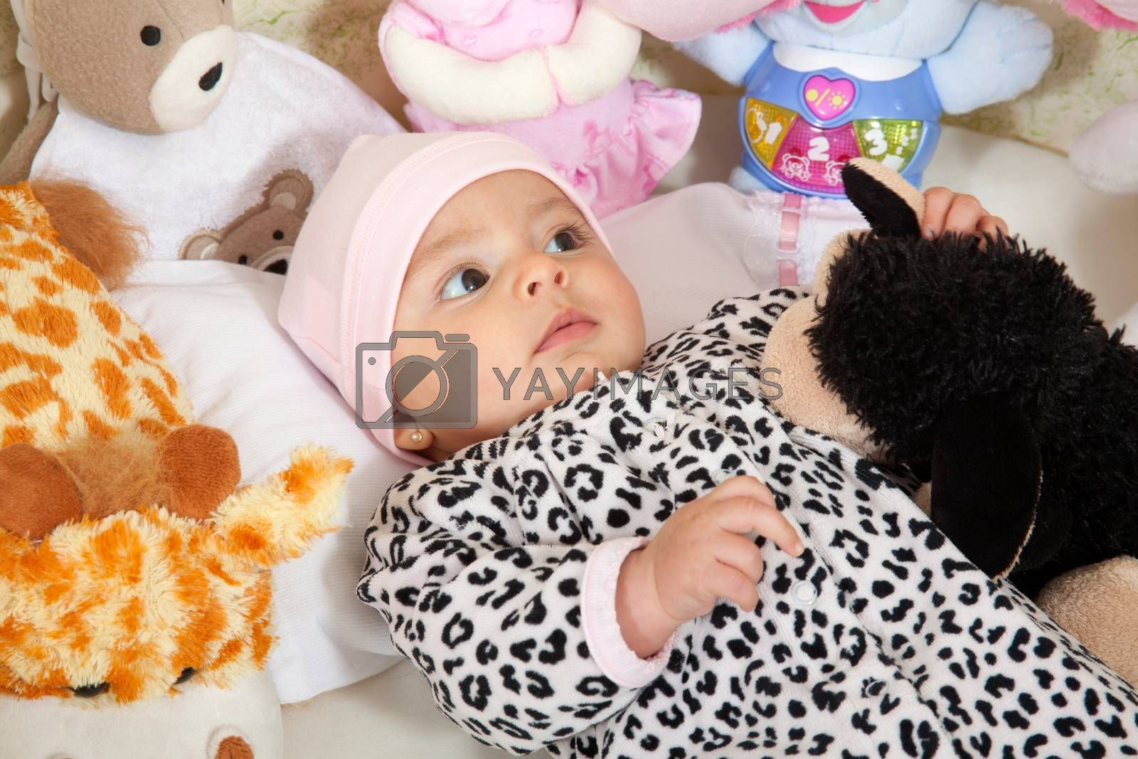 A baby girl dressed in animal print surrounded by stuffed animals
